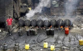 A worker prepares a traditional alcoholic distillate known locally as chang'aa-Kenya Holidays