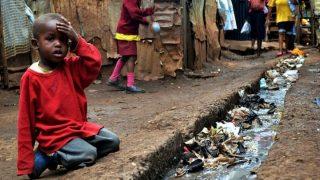 A young boy sits over an open sewer in the Kibera slum Nairobi-Kenya Holidays