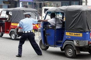 Traffic agent grappling with the driver of a tuk-tuk trying to escape